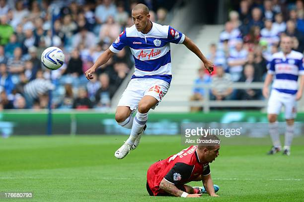 Bobby Zamora of QPR skips over the challenge of Luke Chambers of Ipswich during the Sky Bet Championship match between Queens Park Rangers and...