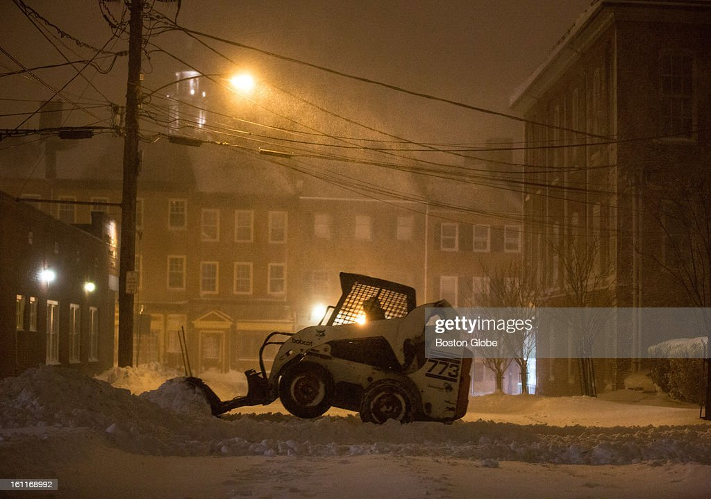 A Bobcat is used to push snow out of a parking lot at 830pm on Essex Street as a winter storm, expected to dump as much as 24 inches of snow in the region, intensified in Newburyport.