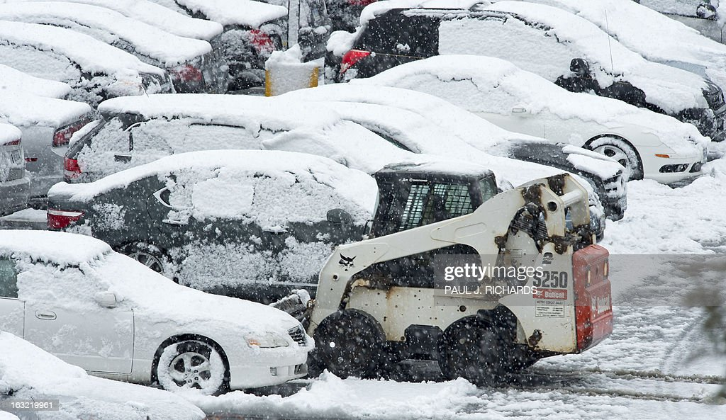 A bobcat tractor removes snow around traveler's cars covered in snow in the parking lot of Dulles International Airport, March 6, 2013, in Sterling, Virginia, a few miles outside of Washington, DC . Federal offices and many schools have closed in preparation for a mix of snow, sleet and rain which could account for the area's largest winter storm in two years. AFP Photo/Paul J. Richards