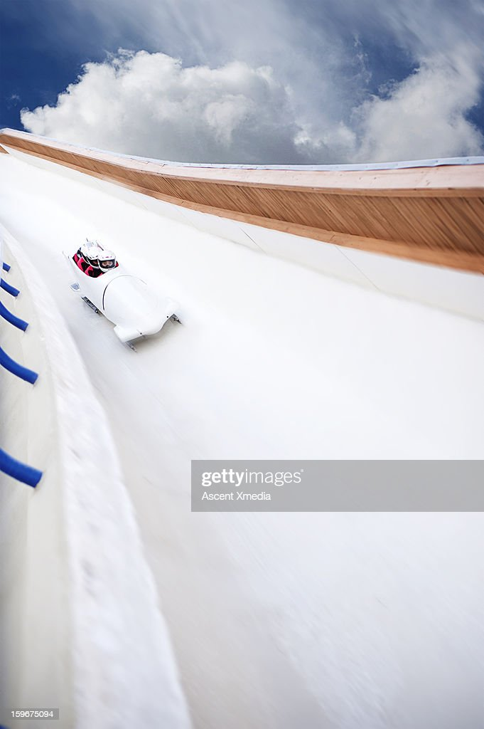Bobsled descends track with speed, clouds behind : Stock Photo
