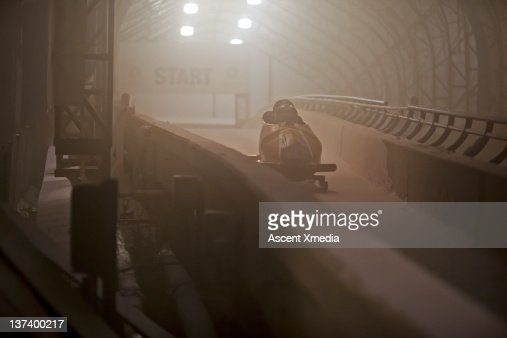 Bobsled leaves start gate for descent along track : Stock Photo