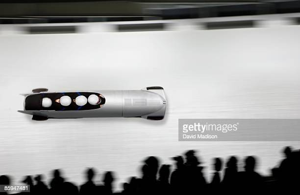Bobsled on track with silhouetted spectators