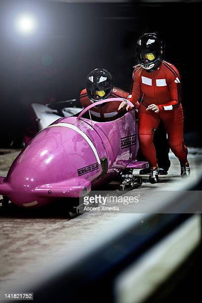 Bobsled racers push sled to start line,competition
