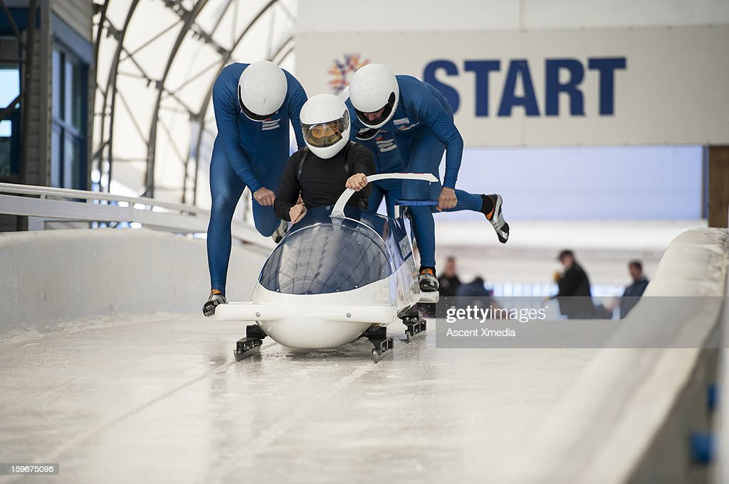 Bobsledders push bobsled out of start gate : Stock Photo
