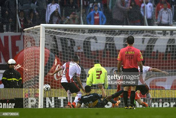 Boca Juniors' defender Lisandro Magallan scores a goal against River Plate during their Argentine First Division football match at the Monumental...