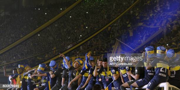 Boca Juniors footballers celebrate after defeating Union and winning Argentina's first division football championship at La Bombonera stadium in...