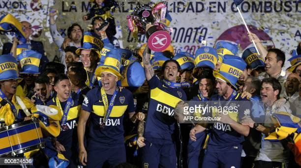 Boca Juniors footballers celebrate with the trophy after defeating Union and winning Argentina's first division football championship at La Bombonera...