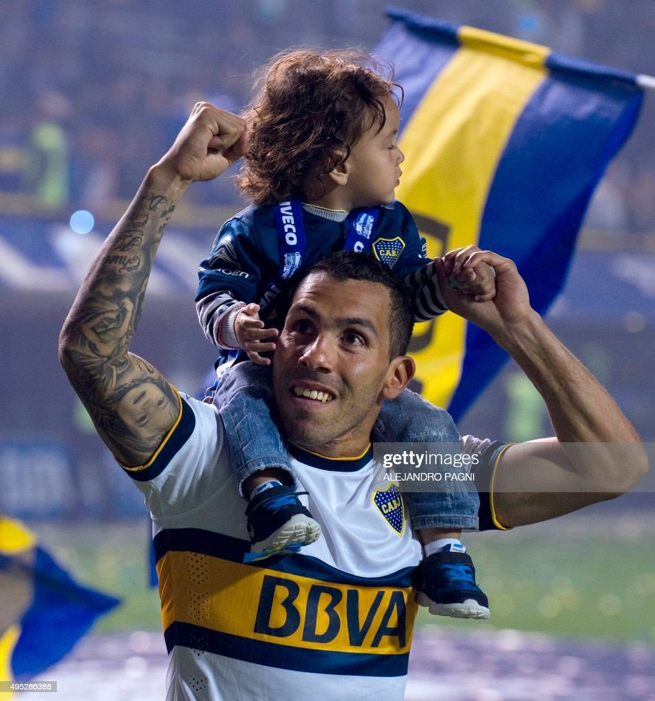 Boca Juniors forward Carlos Tevez celebrates with his son after