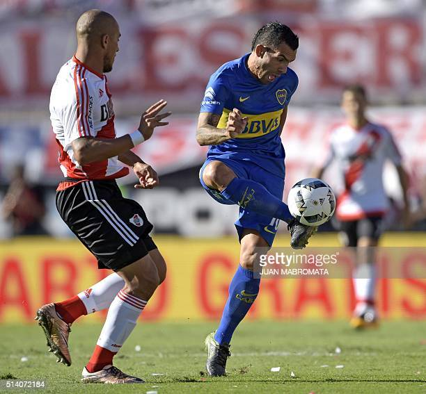 Boca Juniors' forward Carlos Tevez controls the ball next to River Plate's defender Jonathan Maidana during their Argentine first division football...
