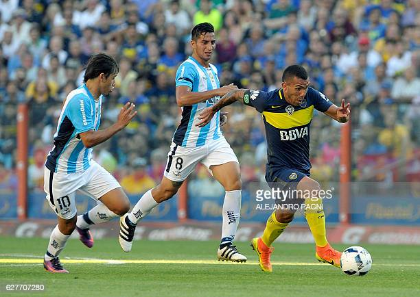 Boca Juniors' forward Carlos Tevez controls the ball past Racing Club's midfielders Oscar Romero and Diego Gonzalez during their Argentina First...
