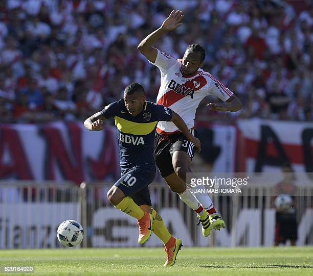 Boca Juniors' forward Carlos Tevez vies for the ball with River Plate's defender Arturo Mina during their Argentine first division football match at...