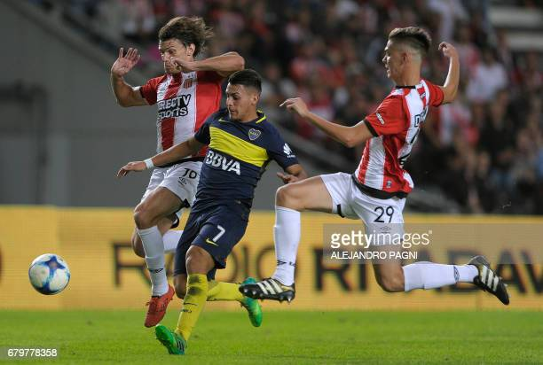 Boca Juniors' forward Cristian Pavon vies for the ball with Estudiantes' defenders Sebastian Dubarbier and Juan Foyth during their Argentina First...