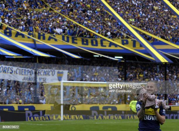 Boca Juniors' forward Dario Benedetto celebrates with his daughter after his team defeated Union and won Argentina's first division football...
