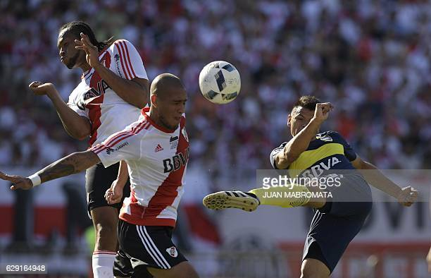 Boca Juniors' forward Walter Bou vies for the ball with River Plate's defender Jonatan Maidana and defender Arturo Mina during their Argentine first...