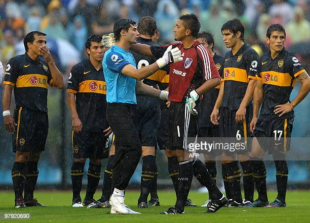 Boca Juniors' goalies Javier Garcia and River's Daniel Vega greet each other before leaving the field after the match was suspended on the ninth...