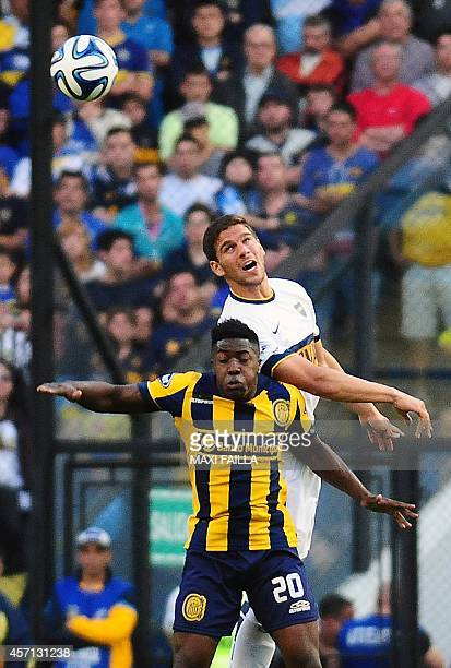 Boca Juniors' Lisandro Magallan jumps for a header with Rosario Central's Jose Valencia during their Argentine First Division football match at the...