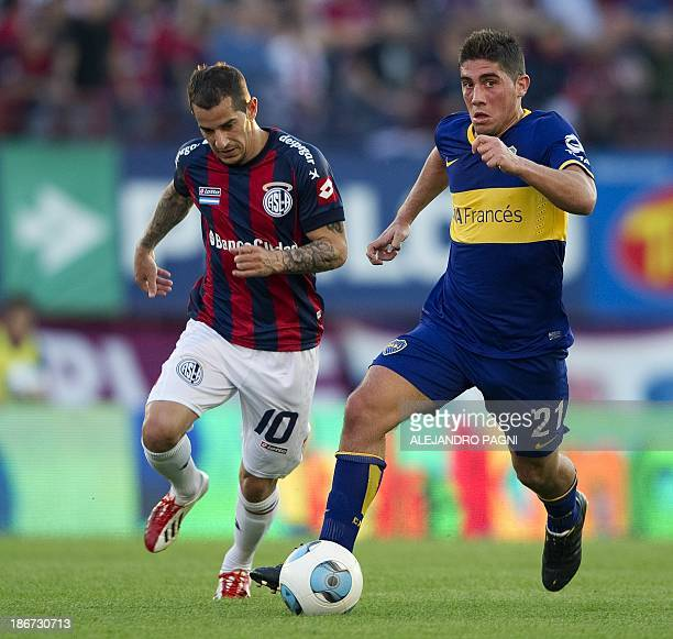 Boca Juniors' midfielder Cristian Erbes controls the ball past San Lorenzo's midfielder Leandro Romagnoli during their Argentine First Division...