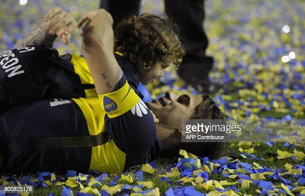 Boca Juniors' midfielder Fernando Gago celebrates with his son after they defeated Union and won Argentina's first division football championship at...