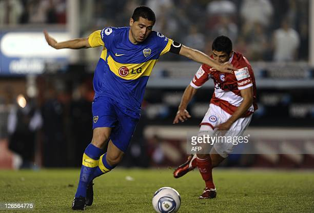 Boca Juniors' midfielder Juan Roman Riquelme prepares to kick the ball past Argentinos Juniors' midfielder Matias Laba during their Argentina First...