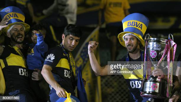 Boca Juniors' midfielder Pablo Perez celebrates with the trophy after they defeat Union and win Argentina's first division football championship at...