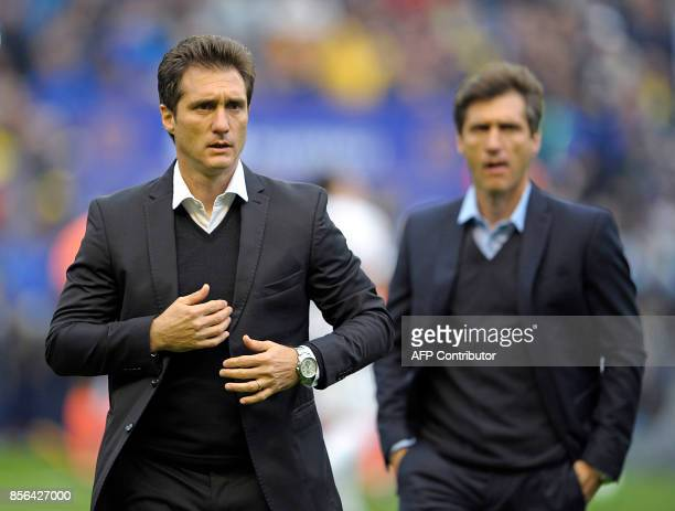 Boca Juniors' team coach Guillermo Barros Schelotto and his brother and assistant Gustavo walk to the bench before the Argentina First Division...