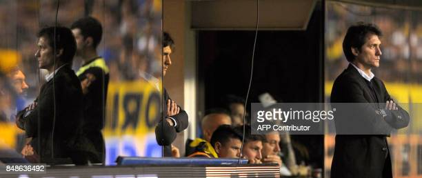 Boca Juniors' team coach Guillermo Barros Schelotto whose image is reflected in the glass to the left and his brother and assistant Gustavo watch the...