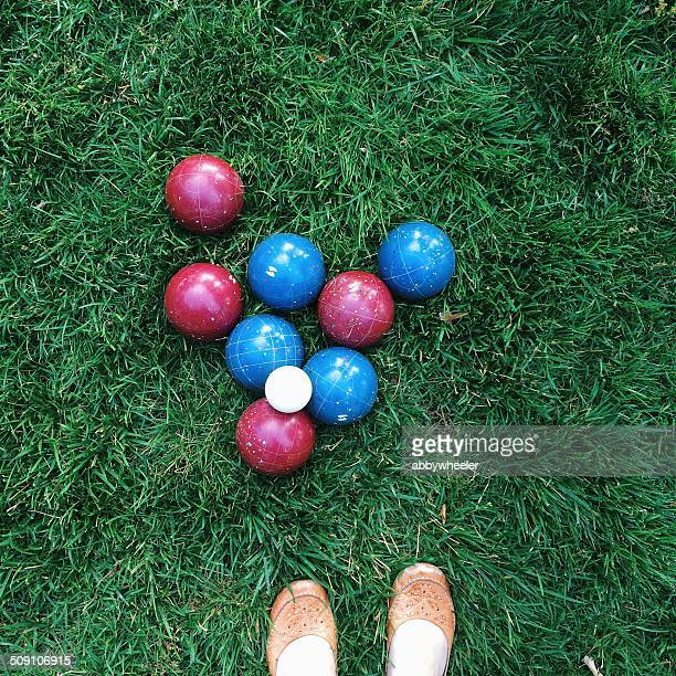 Bocce balls on green grass in park with woman's shoes