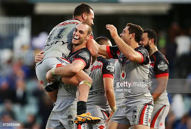 Bodene Thompson of the Warriors celebrates with Simon Mannering R and team mates after scoring the winning try in golden point extra time during the...