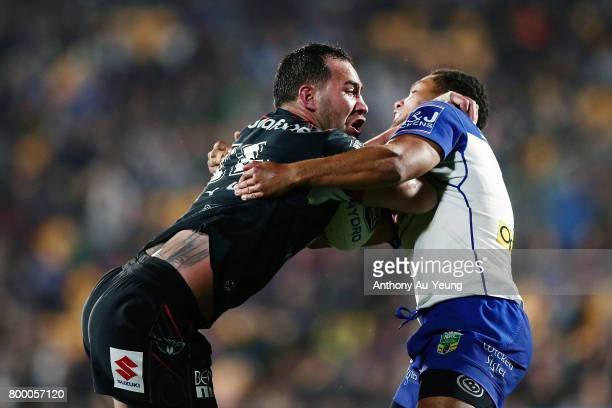 Bodene Thompson of the Warriors fends against Moses Mbye of the Bulldogs during the round 16 NRL match between the New Zealand Warriors and the...