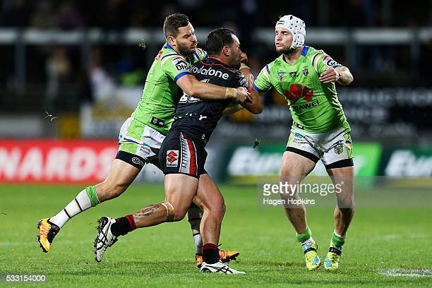 Bodene Thompson of the Warriors is tackled by Aidan Sezer and Jarrod Croker of the Raiders during the round 11 NRL match between the New Zealand...