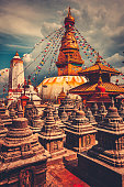 The famous Buddhist stupa at Boudanath in Kathmandu valley, Nepal. Was built in the 14th century. Blue cloudy sky in the background. Travel, holiday. Vintage retro toning filter orange color
