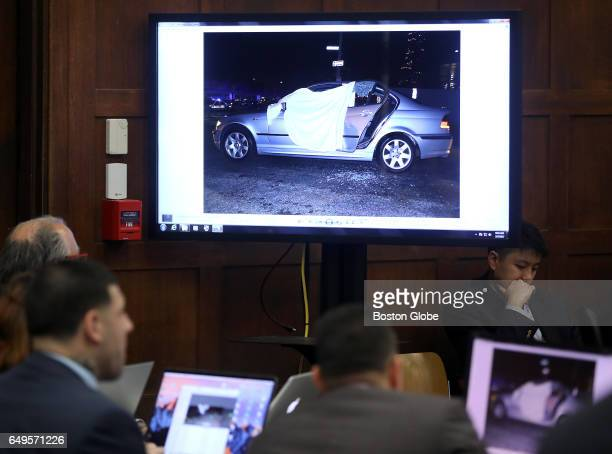 Bodies are covered by sheets in the BMW with window glass on the ground in a photo shown on a monitor in the courtroom as the double murder trial of...