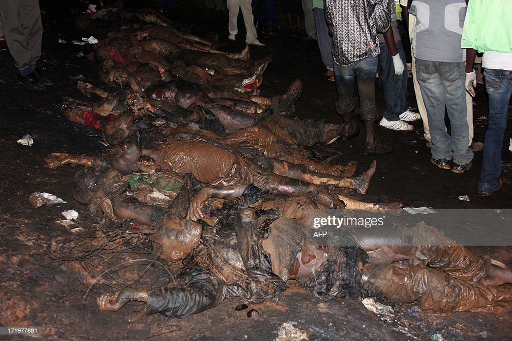Bodies are lined up after a traffic accident involving a fuel tanker and a car on June 29, 2013 in Namungoona, a Kampala suburb. 31 people have so far been pronounced dead and many others are in the hospital with severe injuries, according to a police report.