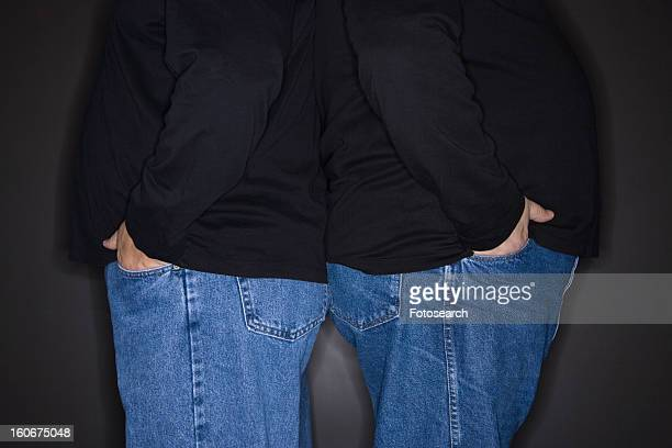 Bodies of mid adult identical twin  men standing back to back.