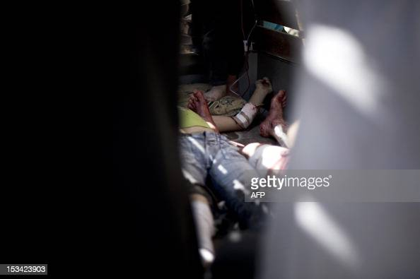 CONTENT Bodies of three members of a Syrian family who were killed in the shelling on a refugee center by government forces lay on a truck outside of...
