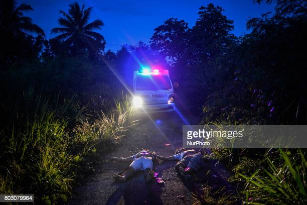 Bodies of two men dumped in an isolated stretch of road are seen in Quezon city north of Manila Philippines June 22 2017 Signs placed over their...