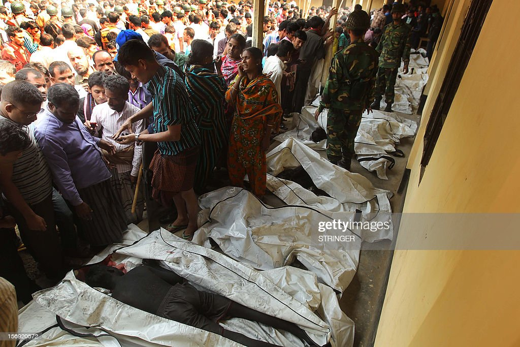 Bodies of victims who died in a fire in a garment factory are lined up in Savar, about 30 kilometres north of Dhaka on November 25, 2012. Rescue workers in Bangladesh recovered 109 bodies on Sunday after a fire tore through a garment factory, forcing many workers to jump from high windows to escape the smoke and flames. AFP PHOTO