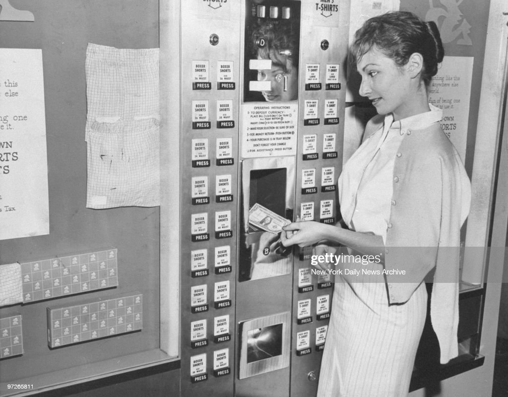 Bodonna Kass inserts a dollar bill into a vending machine that sells men's shorts for 97 cents at Macy's.