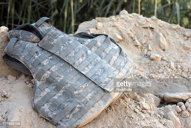 Body armor vest laying on a pile of dirt