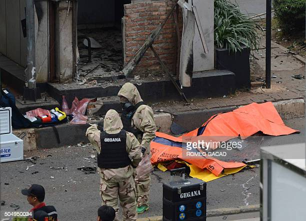 Body bags cover victims outside a traffic police outpost as police secure the area after a series of explosions hit central Jakarta on January 14...