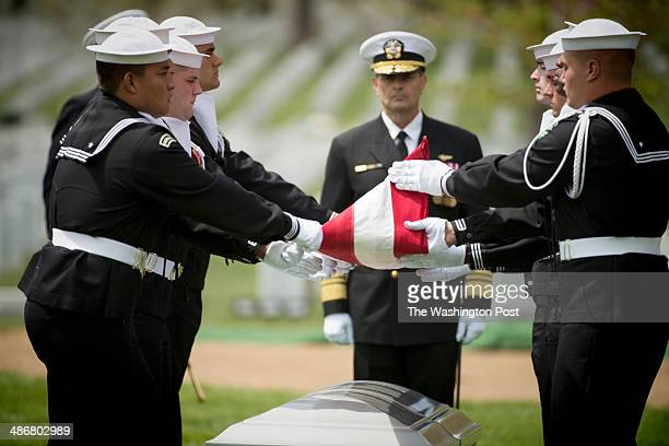 Body bearers with the United States Navy Ceremonial Guard fold the flag during a memorial service for United States Navy MasteratArms 2nd Class Mark...