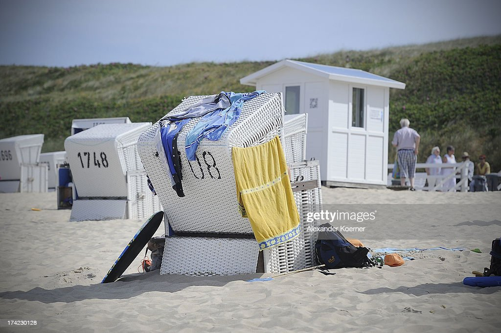 A body board, towels and bags are pictured lying close to a roofed wicker beach chair at the Brandenburger Beach on July 22, 2013 in Westerland, Germany. The weather forecast, for the next three days, predicts sunny weather with heighs of 30 Celsius for the north of Germany.