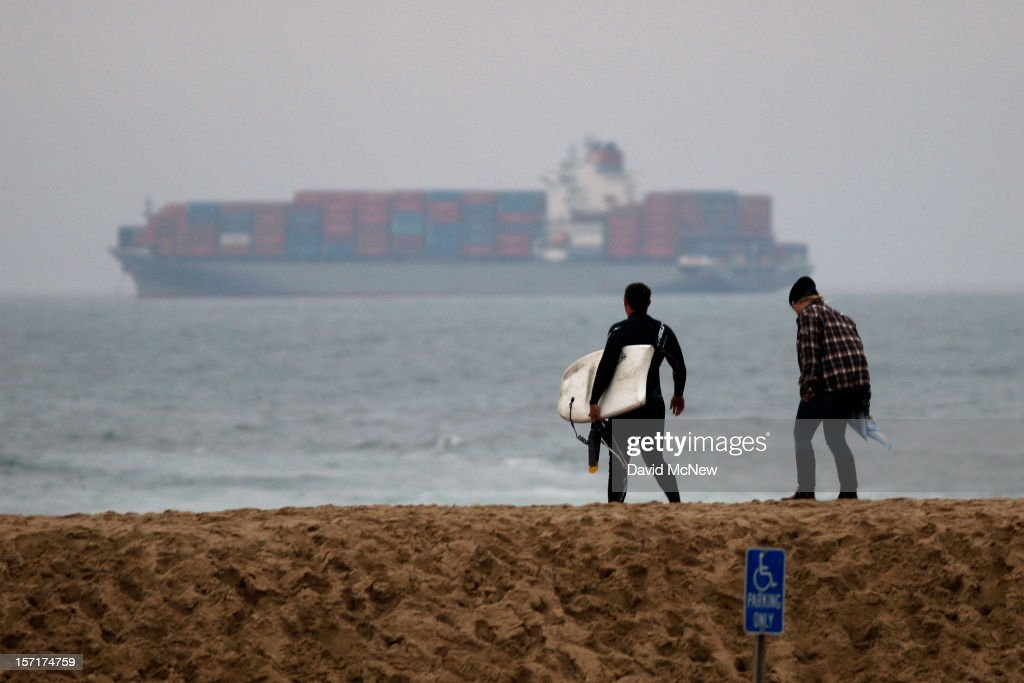 Body boarders cross a sand berm with a view of anchored container ships which cannot enter the ports of Los Angeles and Long Beach to load and unload cargo because of a strike by the International Longshore and Warehouse Union Local on November 29, 2012 in Seal Beach, California. The strike is the largest work stoppage at the ports since a lockout by shipping companies in 2002, which prompted President George W. Bush to intervene with a court injunction to resolve the standoff.