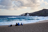 Body boogie boarders enjoy riding in the surf breaking near the shoreline during a blue sunset at Sandy Beach Break Neck Beach Hawaii on the Island...