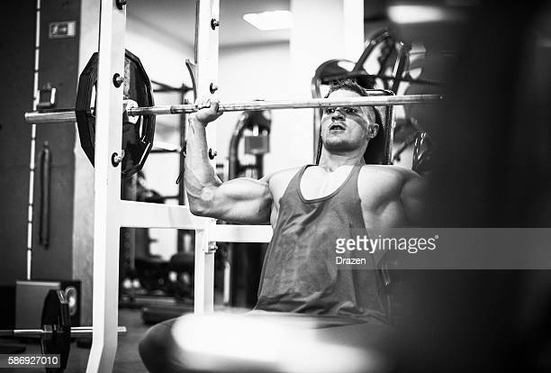 Body builder in gym lifting weights