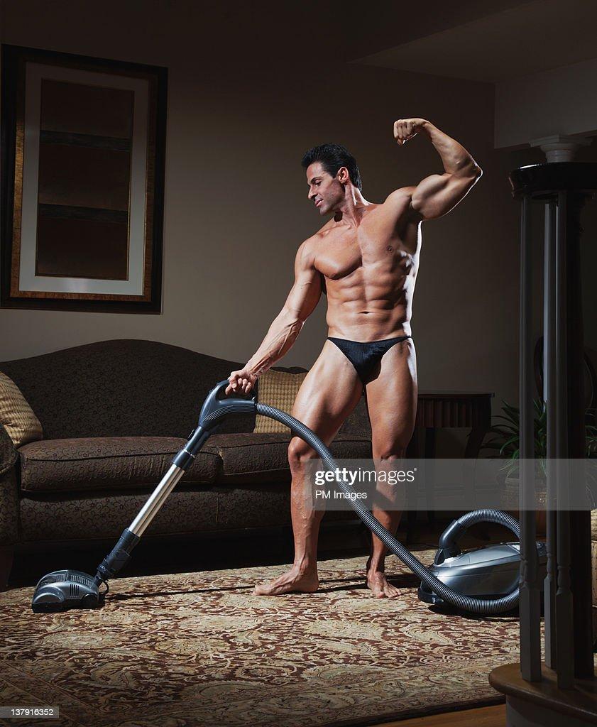 Body builder vacuuming : Stock Photo