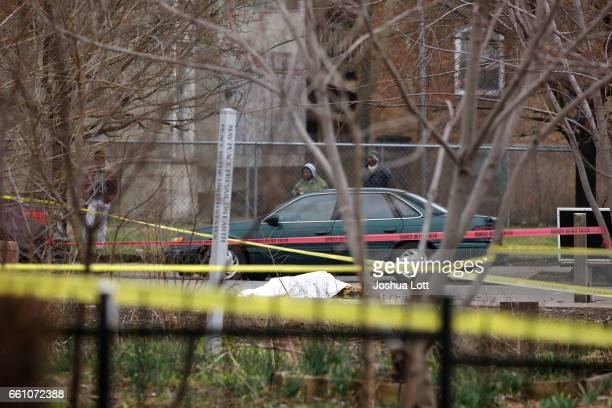 A body covered in a white sheet is surrounded by crime scene tape where four people were shot and killed at a restaurant in the 2700 block of East...