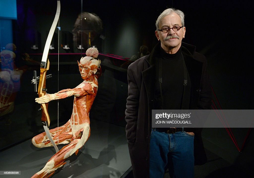 Body donator Holm Gaertner poses in front of a full plastinated of a person training archery on display at the 'Menschen Museum' (Human Being Museum) by plastinator <a gi-track='captionPersonalityLinkClicked' href=/galleries/search?phrase=Gunther+von+Hagens&family=editorial&specificpeople=226597 ng-click='$event.stopPropagation()'>Gunther von Hagens</a> on the eve of its opening in Berlin, on February 17, 2015. German anatomist <a gi-track='captionPersonalityLinkClicked' href=/galleries/search?phrase=Gunther+von+Hagens&family=editorial&specificpeople=226597 ng-click='$event.stopPropagation()'>Gunther von Hagens</a>, dubbed 'Doctor Death' for preserving and displaying dead bodies as artworks, opens a museum dedicated to the technique called plastination, after 20 years of touring the world with this controversial exhibition of human complete corpses and organs.
