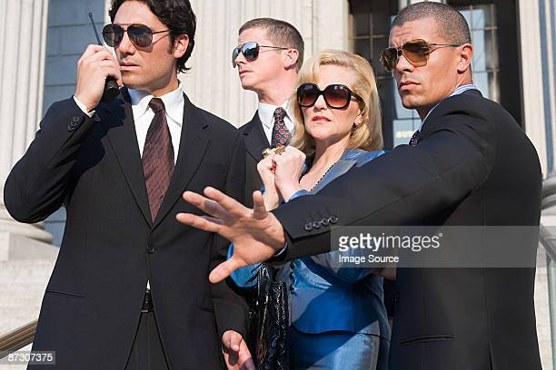 Body guards protecting a woman
