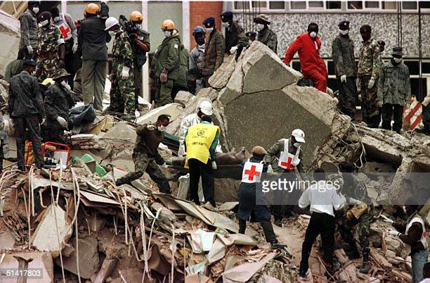 A body is carried 09 August from the wreckage in Nairobi following a bombing near the US Embassy in which 158 people died and 4824 were injured